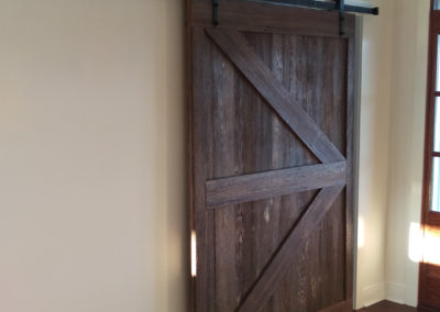 dark brown reclaimed wood gray barn door with custom rails