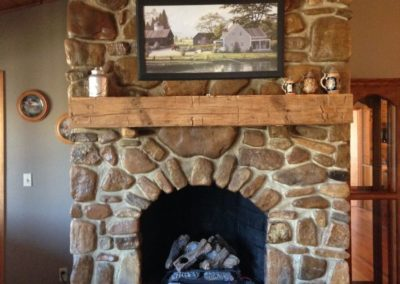 reclaimed gray smooth hand hewn mantle over fireplace