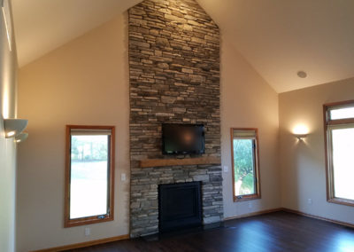 reclaimed hand hewn mantle with stone wall accent