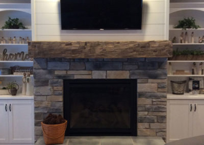 gray smooth hand hewn mantle over fireplace
