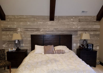 faded white barn siding in bedroom with reclaimed wood ceiling beams