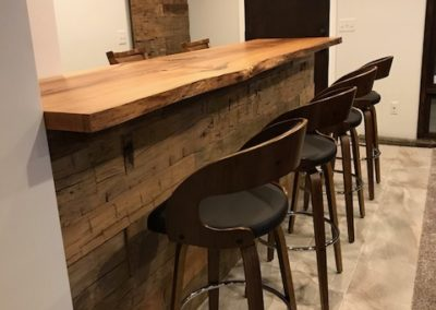 reclaimed live edge bar top with hand hewn skin wall paneling